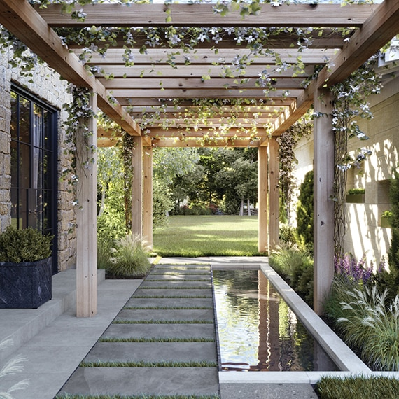 Outdoor courtyard with gray 2CM stone look porcelain pavers, coy pond surrounded by fountain grass, natural wood pergola with flowering vines.