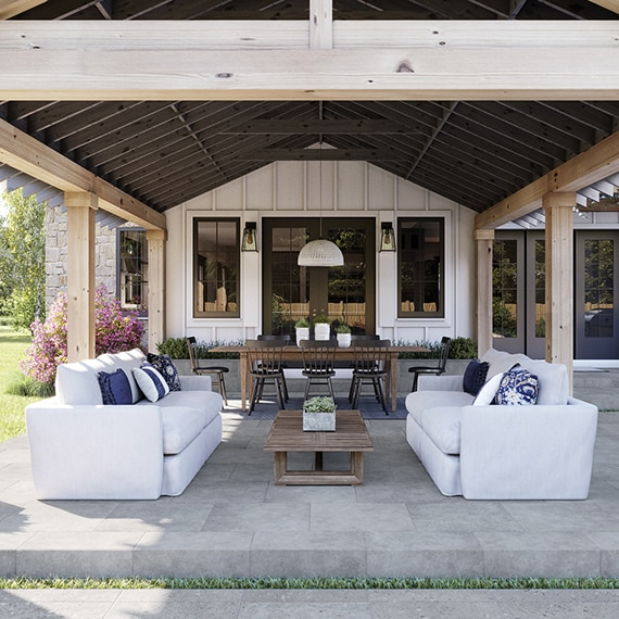 Large covered patio with gray flooring tiles that look like stone, white couches, wood coffee table, pendant light hanging from wood beams over table & chairs.