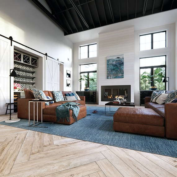 Modern farmhouse living room with herringbone wood look tile flooring, shiplap look porcelain fireplace and black metal vaulted ceiling.