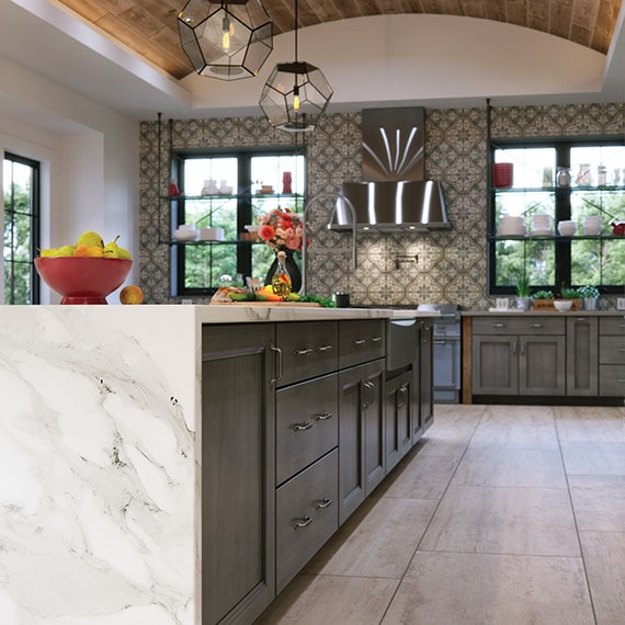 Kitchen with large island. Porcealin tile floors, mosaic tile backsplash, and quartz countertops in a modern farmhouse.