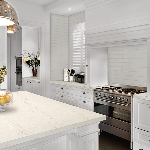 Fresh and clean kitchen décor with white subway tile backsplash, white quartz countertop & island, stainless steel gas stove, and white cabinets.