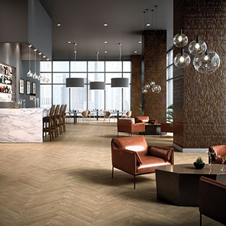 Spacious hotel lobby and bar with wood-look tile floor in a herringbone pattern. Light brown leather modern style low arm chairs and coffee tables on the side.