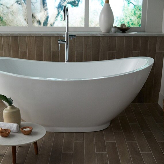 Bathroom with free-standing bathtub in front of picture window, polished silver faucet, wall and floor tiles that look like wood.