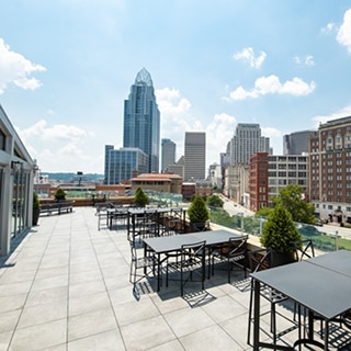 Rooftop restaurant with light beige limestone look 2CM porcelain pavers under black tables & chair with skyscrapers and blue skies in the background.