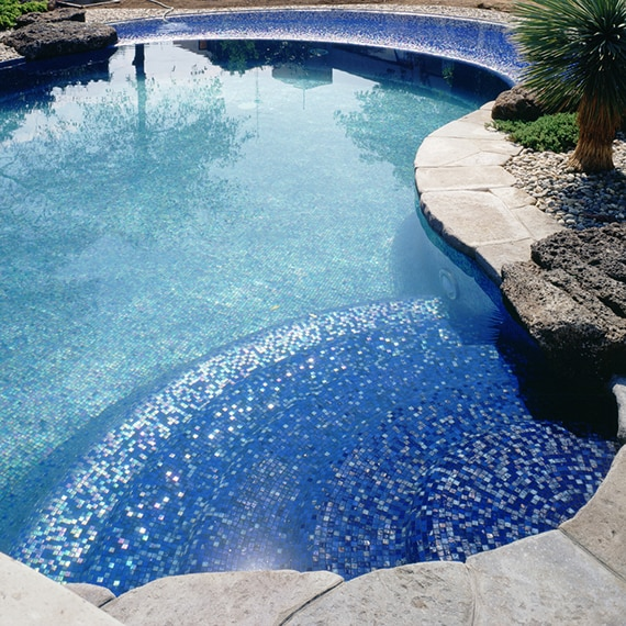 Tropical pool with iridescent blue tile, light gray paver deck, lava rocks, and palm trees set in gravel.