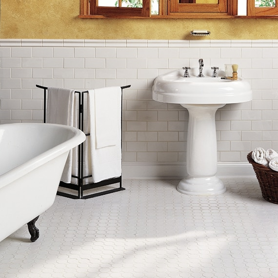 White bathroom with claw-foot tub, white subway tile, white octagon & dot floor tile, freestanding sink and towel rack.