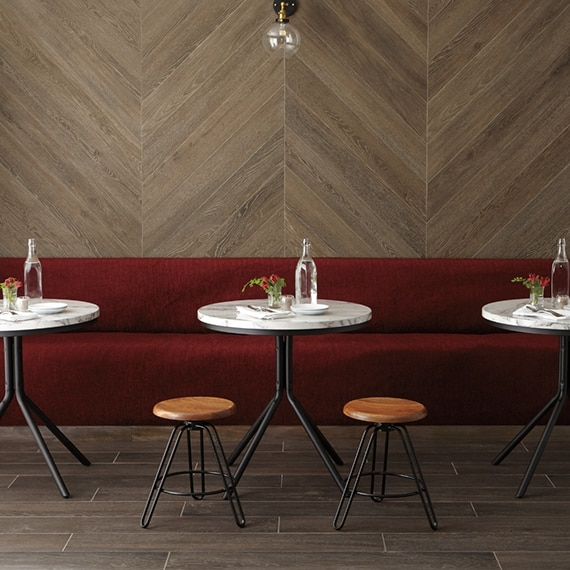 Restaurant dining room with wall-length booth covered in red velvet, herringbone wood look wall tile, marble top table, wood look tile flooring.