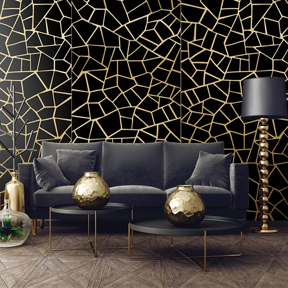 Modern living room with black porcelain slab wall tile with gold random pattern behind a black leather couch, double coffee table holding gold vases, and floor lamp.