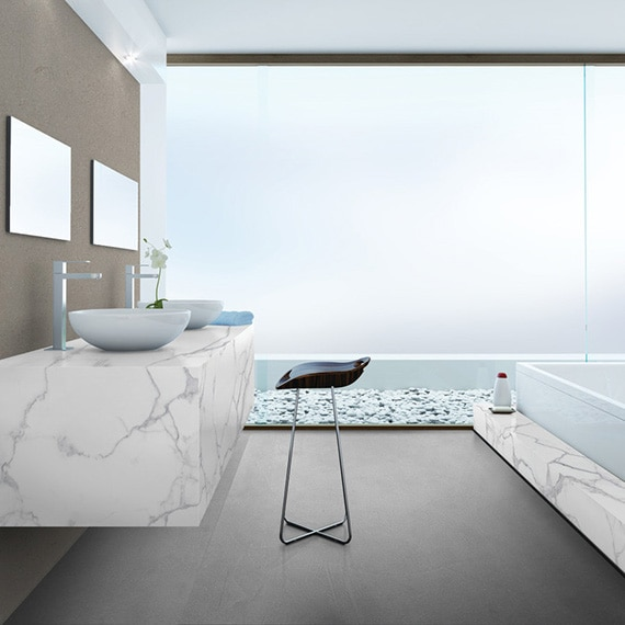 Bathroom with white & gray marble look porcelain slab bathtub surround and matching floating vanity with dual vessel sinks, and large walk-in shower with frosted glass.
