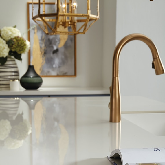 Closeup of white glossy countertop made from large format porcelain slab, brushed brass faucet, and brushed brass caged pendant light.