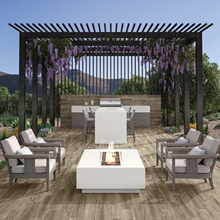 Outdoor patio / kitchen with floor tiles that look like wood, white porcelain slab island and firepit, stainless steel grill, and lavender hanging from pergola.