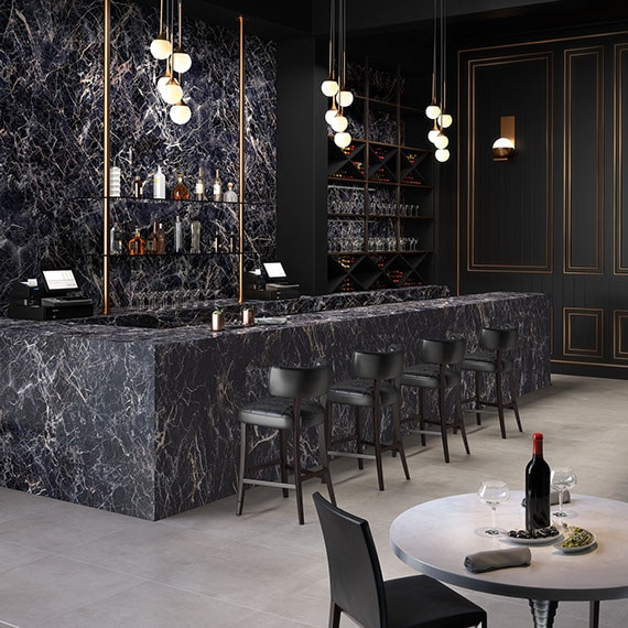 Restaurant bar with black with white veining porcelain slab on the wall, bar top and front, brass and globe pendant lighting, gray stone look flooring tiles.