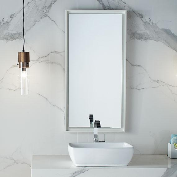 Bathroom vanity with white marble-look, porcelain slab backsplash and countertop, white vessel sink, framed mirror, and pendant lighting.