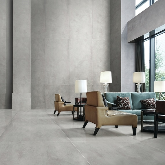 Gray, large format, concrete look tile covers the floor and walls of this lobby with teal couch and tan over-sized chairs.
