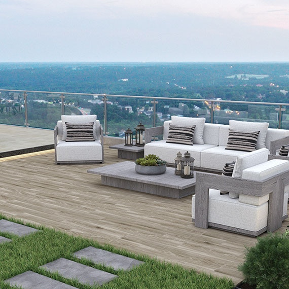 Rooftop patio in a city. Seating area with modern style white and gray furnishings, wood-look slip-resistant tile, and porcelain paver walkway.