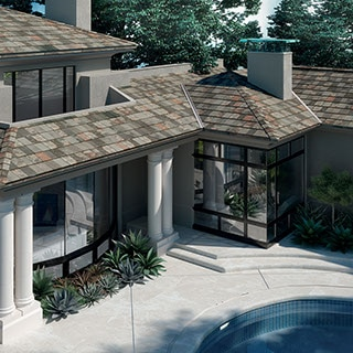 Exterior view of house with several porticos and slate-look porcelain tile roof.