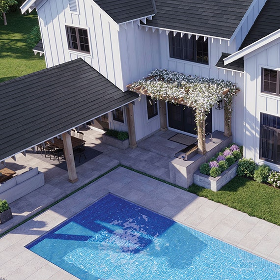 Bird's eye view of modern farmhouse backyard with covered patio, pool, and flower-covered pergola with gray stone look tile flooring.