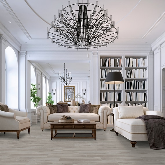Home library with light wood look tile flooring, white overstuffed sofa & chairs, floor-to-ceiling bookshelves, and metal chandeliers.