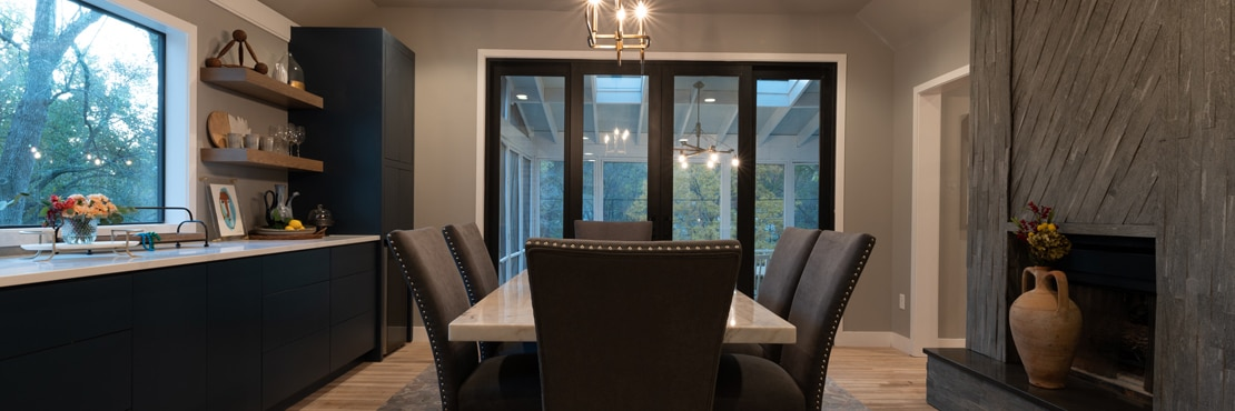 Dining room with white marble table & black cushioned chairs, buffet with white quartz countertop, fireplace with gray stone look tile mantle & soapstone hearth.