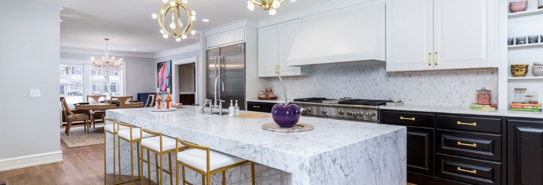 Kitchen with marble mosaic backsplash, white quartz countertops, marble waterfall island with sink, white cabinets, and brushed brass pendant lights.