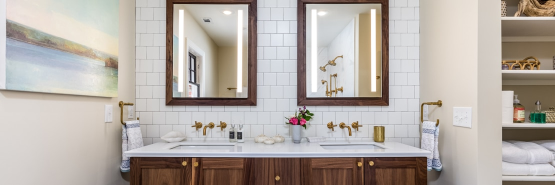 Remodeled bathroom with white square ceramic tile backsplash, natural wood vanity with dual sinks, wood framed mirrors, and brushed brass wall-mounted faucets.