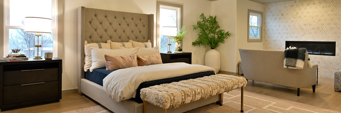 Bedroom with cushioned headboard, nightstands, and wall-mounted fireplace with tan marble and limestone rotating hexagon mosaic wall tile.