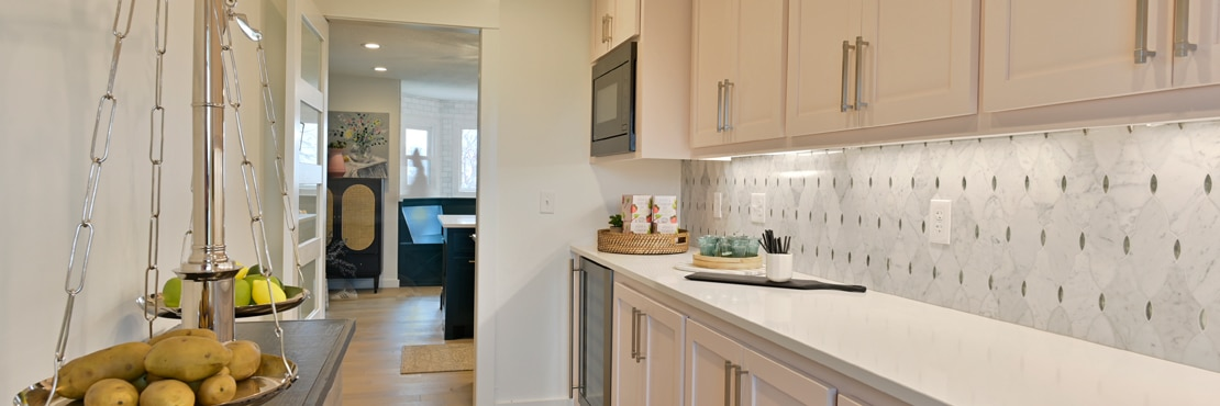 Butler's pantry with white quartz countertop, white & gray marble mosaic backsplash with antique mirror accents, and white wash wood cabinets.