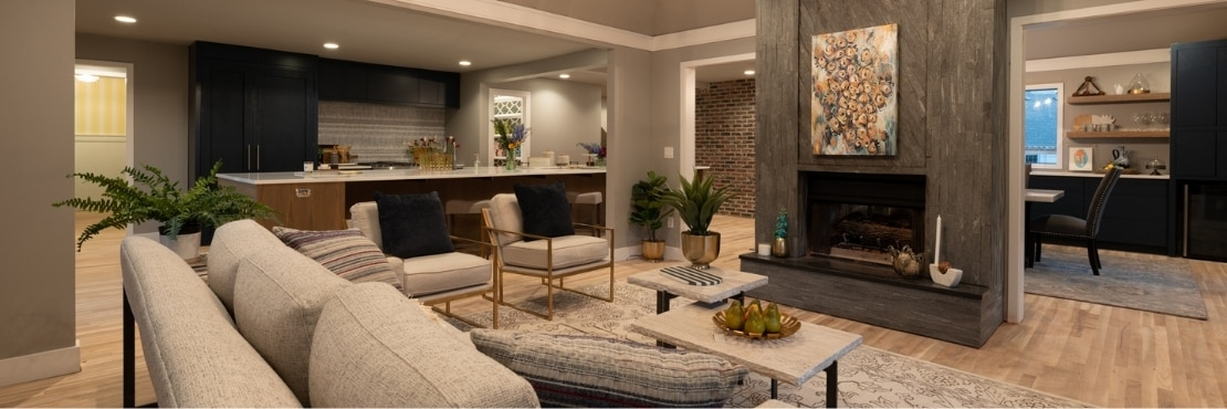 Open concept kitchen/family room with large quartz island, dark gray mosaic fireplace, coffee table, tan overstuffed sofa & side chairs.