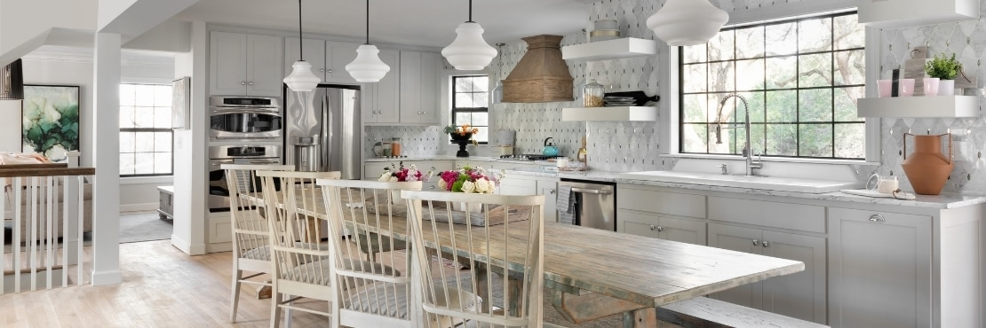 Open concept dining room and kitchen with white & gray marble countertop, antique mirror & marble mosaic backsplash, distressed wood table & chairs.