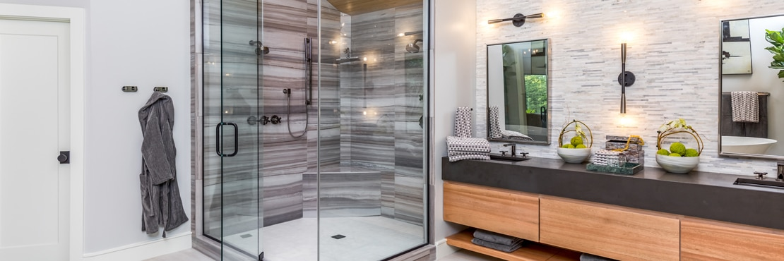 Renovated bathroom with steam shower, brown tile that looks like heavily striated marble, marble mosaic backsplash, and brown quartz vanity countertop.