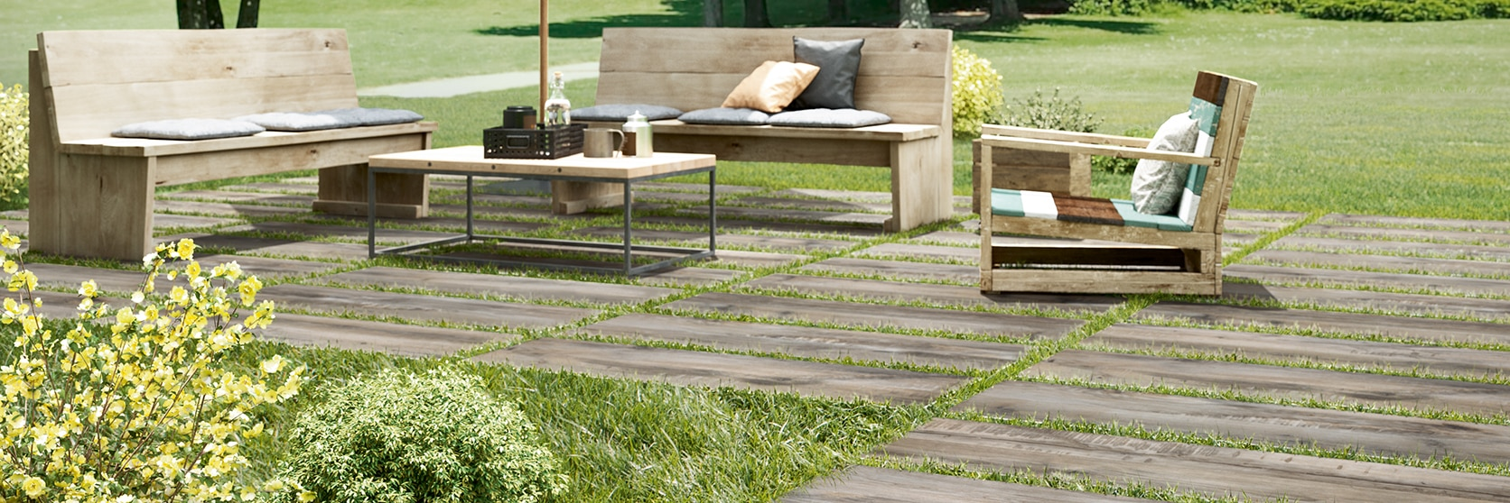 """Lawn furniture on 16"""" x 48"""" 2 centimeter porcelain pavers that look like seasoned wood, set on top of green grass."""