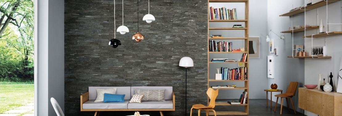 Living room with gray floor tile that looks like stone, dark gray wall tile that looks like stacked stone, wood bookshelves, and pendant lights over a white couch.