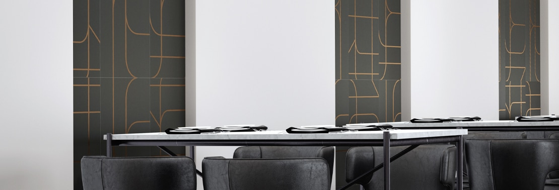 Restaurant dining room with black wall tile with copper designs and white seamless slab wall tile, white tables and black leather chairs.