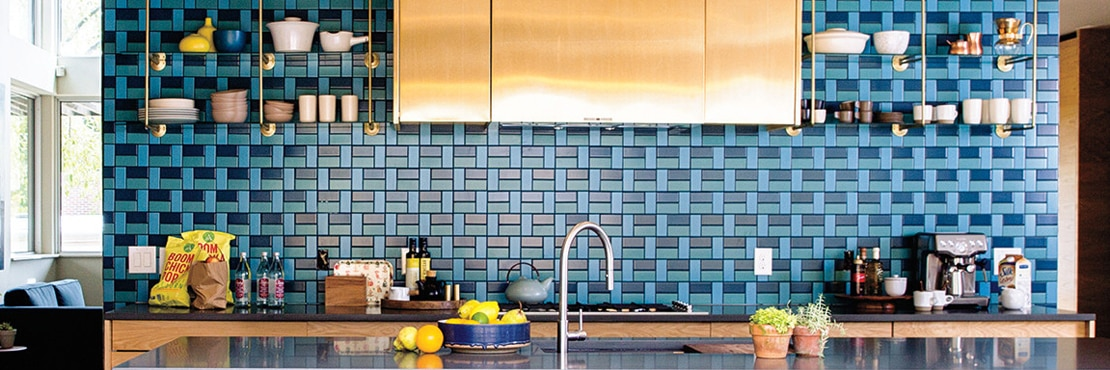 Kitchenette with light and dark blue mosaic backsplash, open shelving, copper vent hood over gas stove, black quartz countertops and island.