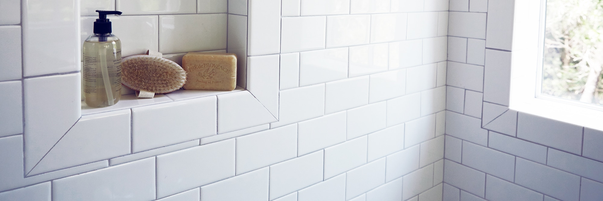 Closeup of shower wall of white subway tile, gray grout, and niche holding a soap dispenser, brush, and bar of soap.