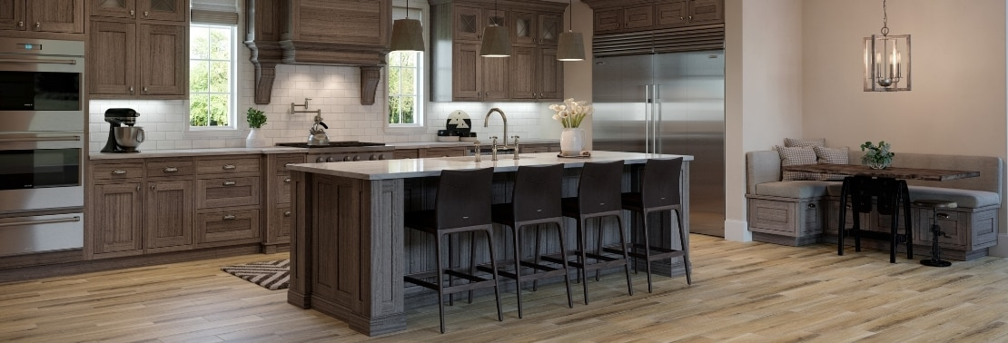 Modern farmhouse kitchen with tile that looks like wood flooring, off-white subway tile, off-white quartzite countertop, natural wood cabinets, and pendants over kitchen island.
