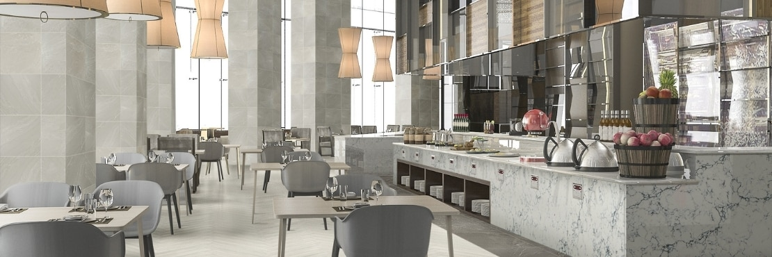 Restaurant dining room with beige stone look tile in a herringbone pattern, columns with stone look tile, gray & beige quartz buffet countertop, pendant lighting hanging over table & chairs.