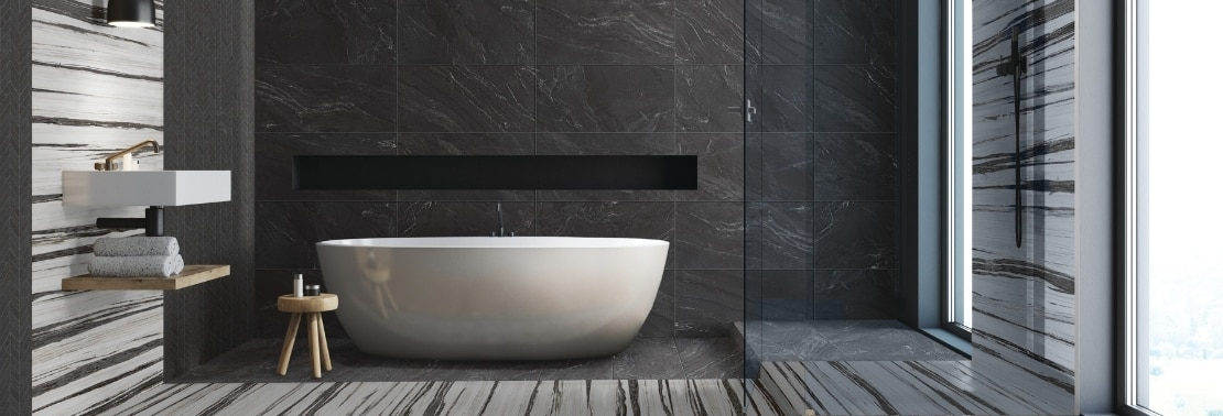 Stunning wet room with free-standing bathtub, shower wall, floor, and niche of black marble look tile with white & black tile accents, black matte shower fixtures, floating vanity countertop & shelf.
