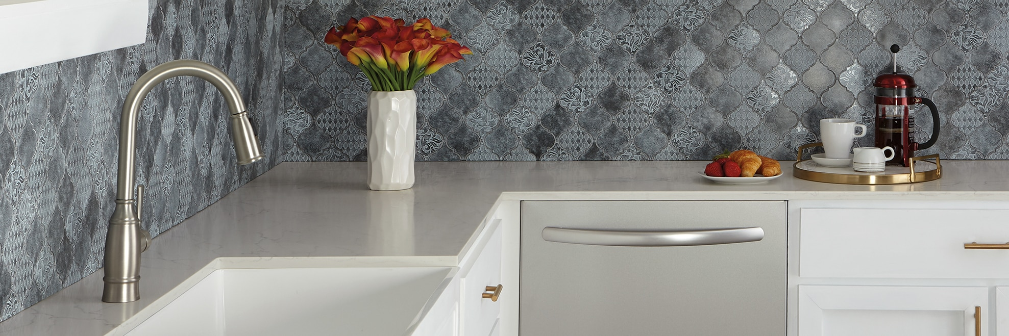 Kitchen backsplash of blue metal arabesque mosaic tile with a bouquet of red calla lilies on an off-white quartz countertop.