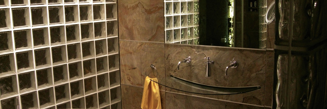 Bathroom with vanity of tan slate stone backsplash, wall-mounted glass sink, wall-mounted polished silver faucet, and glass block wall.