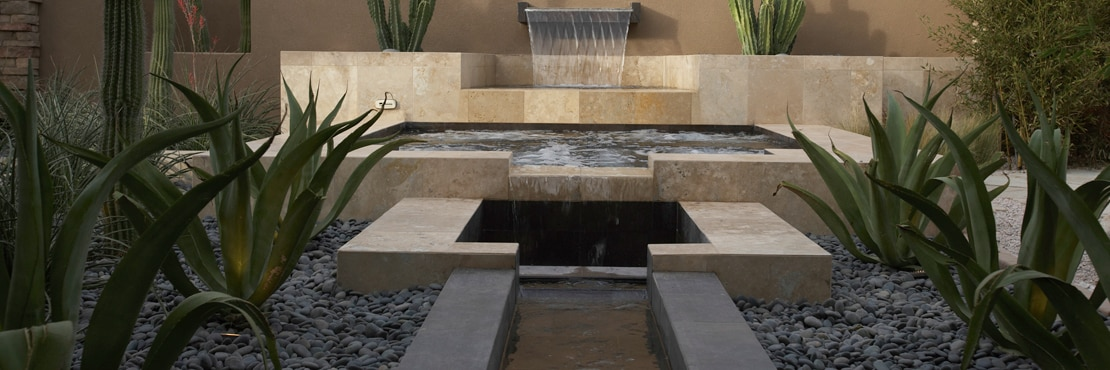 Rustic outdoor pool, spa, and fountain with tan travertine natural stone, aloe, saguaro and senita cactus in ground covered with rocks.