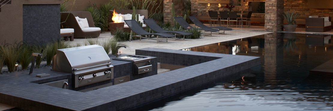 Outdoor pool with swim-up bar & grill with tan travertine natural stone deck, black lounge chairs, wicker loveseats next to firepit and aloe, saguaro and senita cactus.
