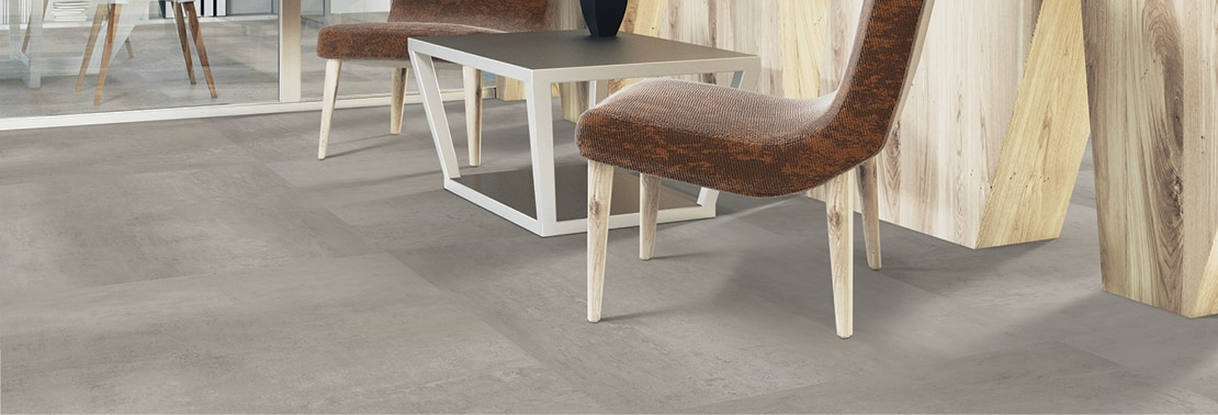 Closeup of flooring of office foyer with luxury vinyl tile that looks like gray concrete flooring, brown leather chairs and side table in front of natural wood panel wall.