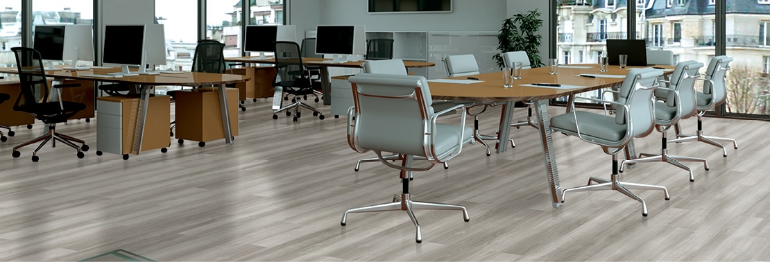 Open concept office with luxury vinyl tile that looks like white oak wood flooring, desks the computers & rolling chairs, conference table with pale blue leather rolling chairs.