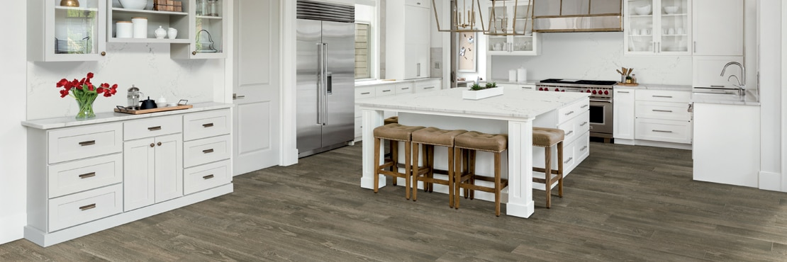 Transitional kitchen with floor tile that looks like wood, white cabinets, white quartz with gray veining countertops, island, and backsplash.