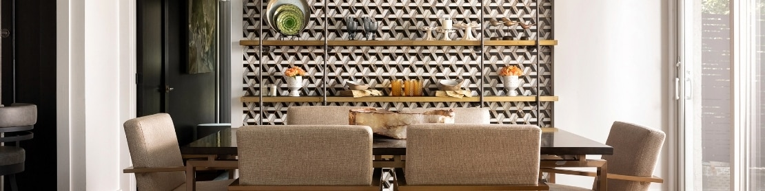 Dining room with table & chairs and feature wall with floor-to-ceiling white, gray & black mosaic tile and brass shelving.