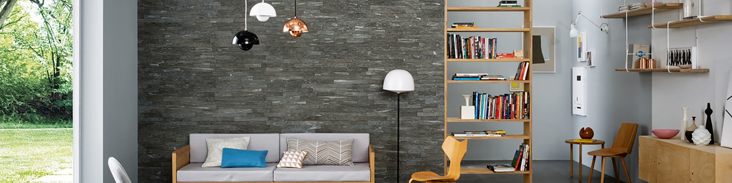 Family room with gray stacked stone feature wall, white, black and copper pendant lighting, gray sofa, bookshelves, and open patio door.