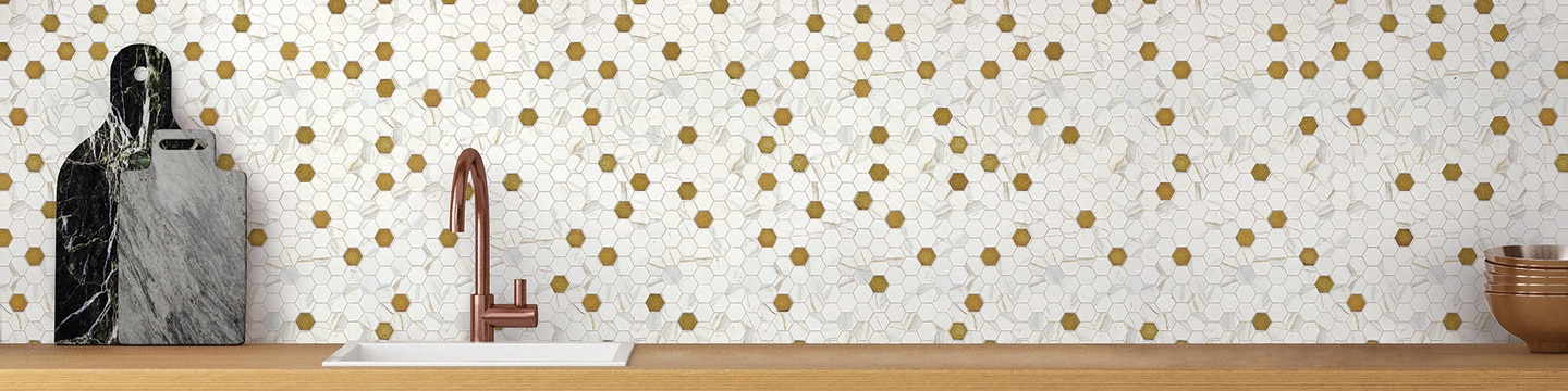 Kitchen backsplash of white marble look & gold hexagon mosaic glass tile, butcherblock countertop, sink with copper faucet, and copper mixing bowls.
