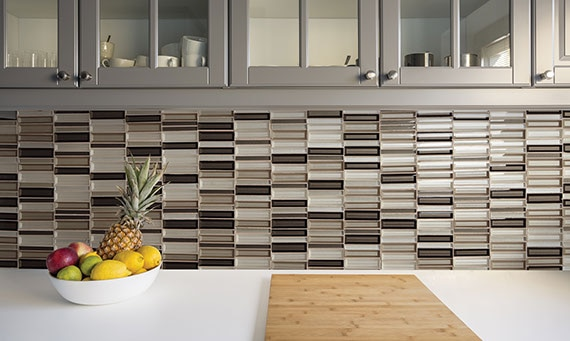 Varigated taupe, brown, and beige glass mosaic kitchen backsplash with gray cabinets and white countertop with a bowl of fruit.