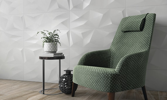 Green high back cushioned chair in front of white textured feature wall, houseplant on small side table, and floor tile that looks like seasoned wood flooring.
